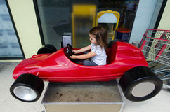 Child drive a toy car. Little girl drive  a toy sport car Royalty Free Stock Image