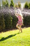 Little girl driving a car. Little girl has fun playing with water on sunny day Stock Images