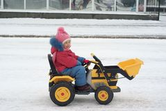 Little girl driving toy electric excavator. In winter Stock Photos
