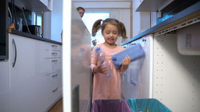 Little Girl Drops The Trash Into Kitchen Recycling Bin. Dolly. Shot stock footage