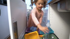 Little Girl Drops The Trash Into Kitchen Recycling Bin. Slow motion. Little Girl Drops The Trash Into Kitchen Recycling Bins. Slow motion stock footage