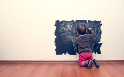 Little girl drowing on the wall. Cute and little girl learn to draw on the walls stock images