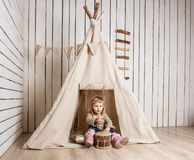 Little girl with drum near wigwam Royalty Free Stock Photos