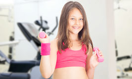 Little girl with dumbbells Stock Images