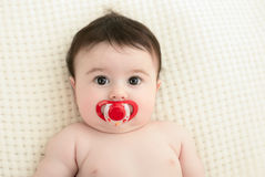 Portrait of a baby. Little girl with dummy in mouth Stock Photo