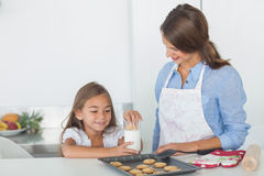 Little girl dunking a cookie into a glass of milk Stock Photos