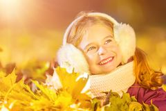 Little girl in earflaps playing with autumn leaves Stock Image
