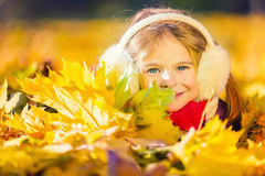 Little girl in earflaps playing with autumn leaves Stock Photo