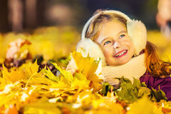 Little girl in earflaps playing with autumn leaves Royalty Free Stock Image