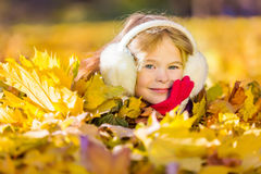Little girl in earflaps playing with autumn leaves. In the park Royalty Free Stock Photo
