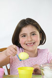 Little Girl at Easter. Little Girl Coloring Easter Eggs Royalty Free Stock Photos