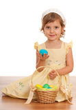 Little girl with Easter basket. A little girl sitting on the floor near the Easter basket and holding an egg Royalty Free Stock Photo