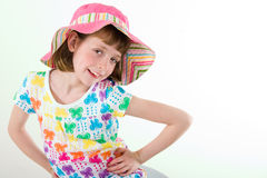 Little Girl in Easter Bonnet. Little girl wearing colorful hat, sitting, leaning to the left, hands on hips, isolated on white Royalty Free Stock Photo