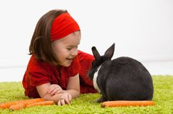 Little girl with Easter bunny. Easter image: smiling little girl with Easter bunny on green carpet royalty free stock photos