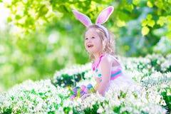 Little girl at Easter egg hunt Stock Photo