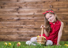 Little girl with Easter eggs. On the background of wooden wall Royalty Free Stock Images