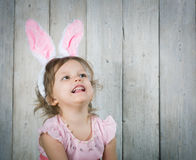 Little girl with Easter eggs. On the background of wooden wall Stock Photos