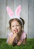 Little girl with Easter eggs. On the background of wooden wall Royalty Free Stock Image
