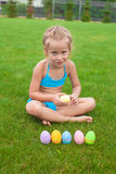 Little Girl with Easter eggs on the grass in her Stock Images