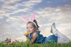 Little girl with Easter eggs. On the grass at sunset Stock Photography