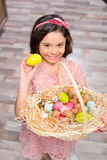 Little girl with Easter eggs. Little girl holding basket full of colorful Easter eggs and smiling at camera Stock Images