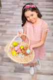 Little girl with Easter eggs. Little girl holding basket full of colorful Easter eggs and smiling at camera Royalty Free Stock Photo