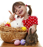 Little girl with easter rabbits and eggs. Happy little girl with easter rabbits and eggs Royalty Free Stock Images