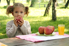 Little girl eat apple in park Stock Photography