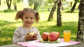 Little girl eat apple stock video