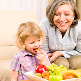 Little girl eat apricot fruit with grandmother. Relaxing on sofa Royalty Free Stock Images