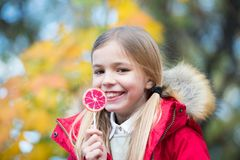 Little girl eat candy on stick, food. Child smile with lollipop, snack. Food, snack, dessert for small child on nature. Happy chil. Dhood and youth. Kid beauty Stock Image
