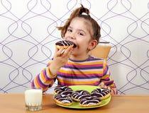 Little girl eat donuts Stock Photo
