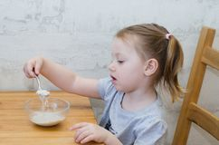 Little girl eat her porridge. Little kid  wants to eat porridge at the table stock photos