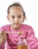 Little Girl Eat Honey Stock Images