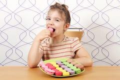 Little girl eat macaroons Stock Photos