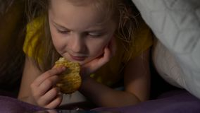 Little girl eat at night. Watching cartoons video eating cracker snack lying on the bed with smartphone child little girl caucasian white european 5 years old stock video footage