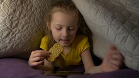 Little Girl Eat With Phone. Watching cartoons video night eating snack lying on bed smartphone caucasian white european 5 years old yellow t shirt stock video footage