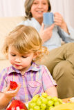Little girl eat strawberry fruit with grandmother Stock Images