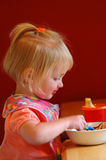 Little Girl Eating. Little girl with bib eating from bowl Royalty Free Stock Photo
