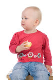 Little girl eating an apple. Baby sitting on a chair and eating an apple Stock Photo