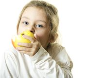 Little girl  eating an apple. Little girl with blue eyes eating an apple Royalty Free Stock Photography