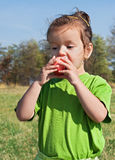 Little girl eating apple Stock Image