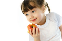Little girl eating an apple stock photo