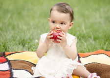 Little girl eating an apple. Cute girl eating an tasty apple royalty free stock image