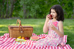 Little girl eating apple at picnic Royalty Free Stock Photo