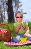 Little girl eating apple at picnic Stock Photo