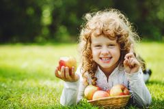 Little girl is eating apple and smiling showing white teeth. Child with a gesture of attention stock image