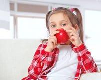 Little girl eating apples Stock Photos