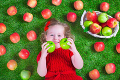 Little girl eating apples Stock Photography