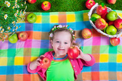 Little girl eating apples Stock Images